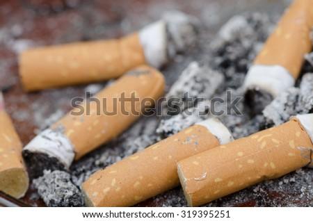 cigarette stubs in ashtray closeup - stock photo