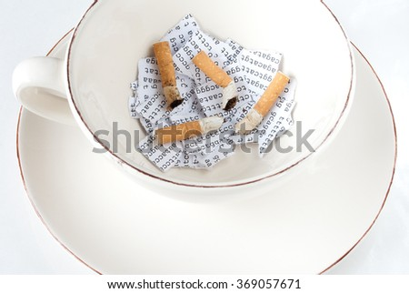 Cigarette stubs on a torn DNA sequence in a coffee cup - stock photo