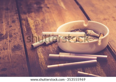 cigarette with ashtray on wood table - stock photo