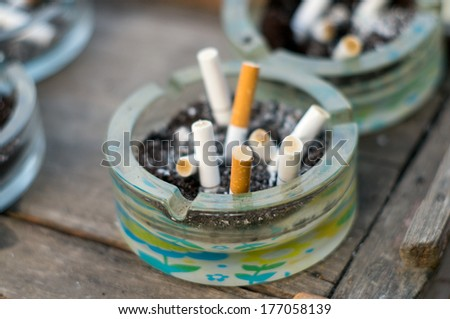 Cigarettes in a dirty ashtray - stock photo