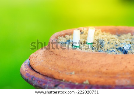Cigarettes in ashtray with green background - stock photo