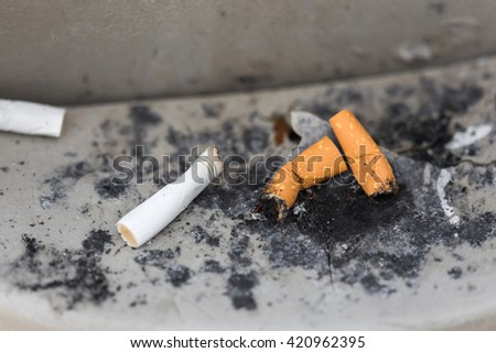 Cigarettes in outdoors ashtray, closeup - stock photo