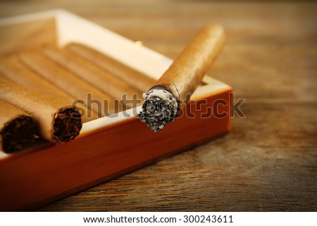 Cigars and burning one on wooden table, closeup - stock photo