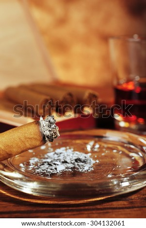 Cigars and burnt one with ash and cognac on wooden table, closeup - stock photo