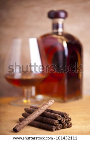 cigars and cognac on a wooden background
