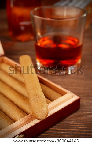 Cigars in humidor with cognac on wooden table, closeup - stock photo