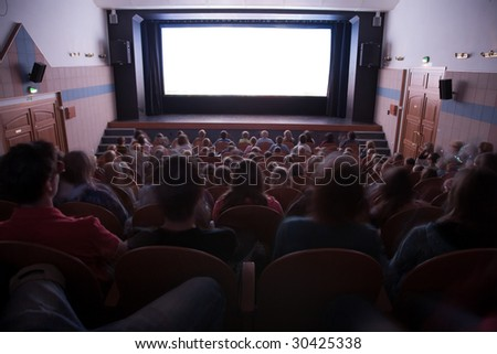 Cinema auditorium with people in chairs watching movie performance. Ready for adding your own picture. - stock photo