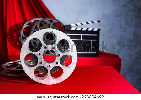 Cinema clapper and reel on the background of red curtain - stock photo