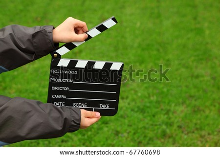 Cinema clapper board in hands of boy in jacket on field with green grass - stock photo