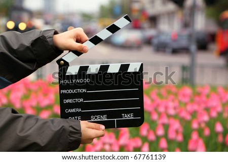 Cinema clapper board in the hands of boy on field with tulips on urban streets