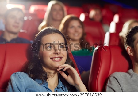 cinema, entertainment and people concept - happy friends watching comedy movie in theater - stock photo