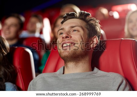 cinema, entertainment and people concept - happy young man watching comedy movie in theater - stock photo