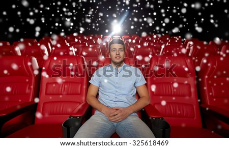 cinema, entertainment and people concept - happy young man watching movie alone in empty theater auditorium over snowflakes - stock photo