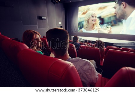 cinema, entertainment, communication and people concept - happy couple of friends watching movie and talking in theater from back - stock photo