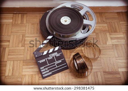 Cinema movie clapper board and 35 mm film reel on wooden floor vintage color effect - stock photo