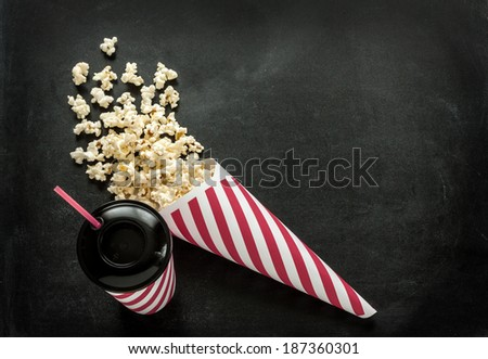 Cinema snacks - cornet popcorn and drink in paper cup with a straw on black chalkboard. Background layout with free text space. - stock photo