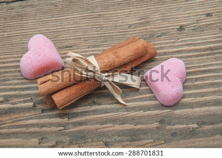 cinnamon and fruit candy in the form of heart on a wooden background - stock photo