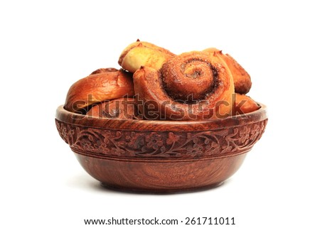 Cinnamon buns in the wooden bowl isolated on white background - stock photo
