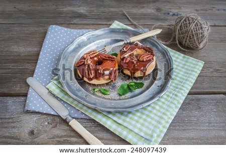 Cinnamon donuts with caramel icing and pecans served with fresh mint and cane sugar on a vintage metal plate over table napkins and a rustic wood background - stock photo