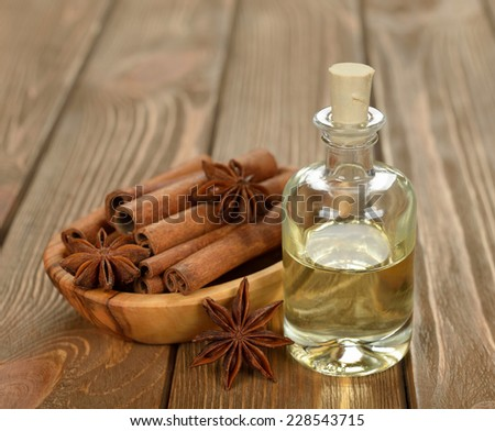 cinnamon essential oil on brown background - stock photo