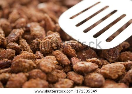 Cinnamon Glazed almonds composed with a spatula. - stock photo