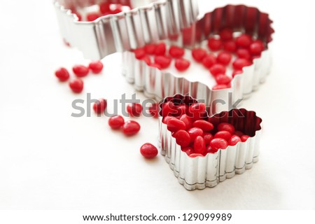 Cinnamon heart candy and heart shaped cookie cutters - stock photo