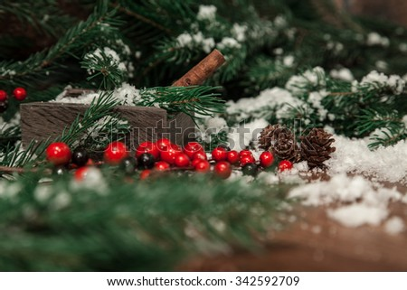 cinnamon in a box against a blurred background of fir branches and holly berries. vintage Christmas - stock photo