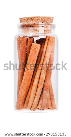 Cinnamon in a glass bottle with cork stopper, isolated on white. - stock photo