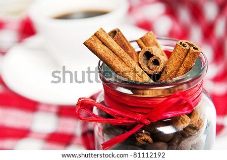 cinnamon  in the pot on a red tablecloth - stock photo