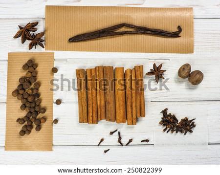 Cinnamon, nutmeg, cloves, allspice, vanilla sticks. Spices on the wooden background - stock photo