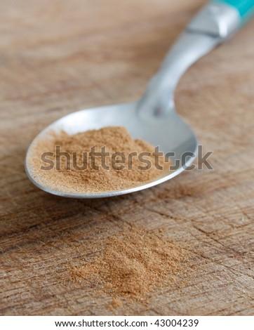 Cinnamon on a spoon on a bg - stock photo