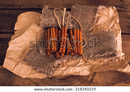 Cinnamon on the wooden background. Cinnamon sticks on a crumpled paper.