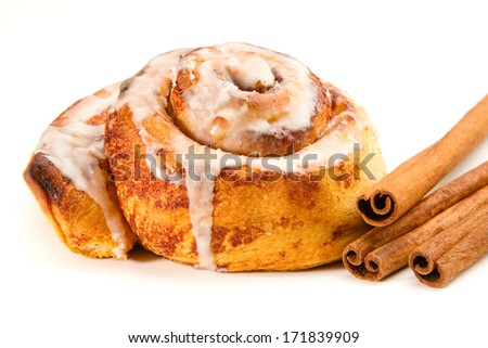 Cinnamon Roll - This is a photo of a tasty cinnamon roll coated in icing and a few cinnamon sticks. Shot with a shallow depth of field on an isolated white background. - stock photo