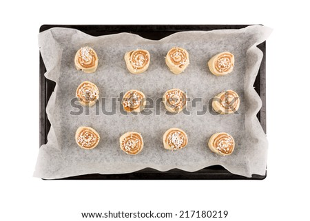 cinnamon rolls dough on a baking plate and baking paper waiting for bake of.  - stock photo