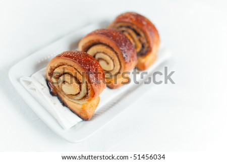 Cinnamon Rolls: small spiral twisted buns stuffed with a buttery cinnamon and brown sugar cream. Shallow depth of field on the first roll - stock photo