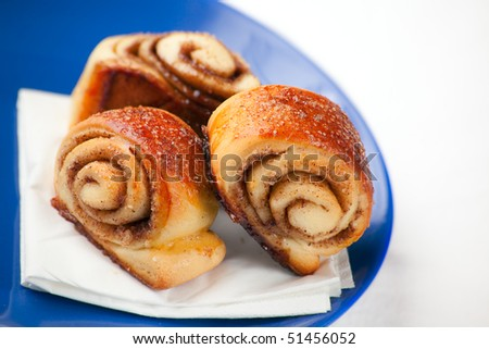 Cinnamon Rolls: small spiral twisted buns stuffed with a buttery cinnamon and brown sugar cream. Shallow depth of field on the first rolls - stock photo