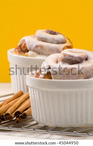 cinnamon rolls with cinnamon sticks on a yellow background - stock photo