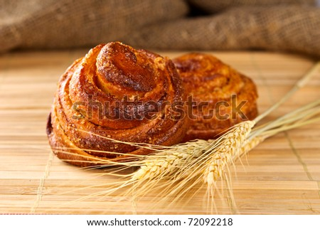 Cinnamon rolls with ear of wheat closeup - stock photo