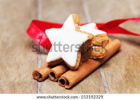 cinnamon star on cinnamon sticks with a red ribbon on wooden background - stock photo