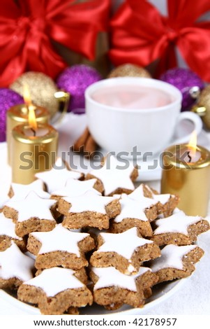 Cinnamon, star shaped christmas cookies with icing with a cup of hot cocoa and gold candles with christmas balls and gifts in the background - stock photo