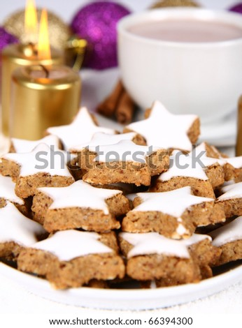 Cinnamon, star shaped christmas cookies with icing with a cup of hot cocoa and gold candles with christmas balls in the background - stock photo