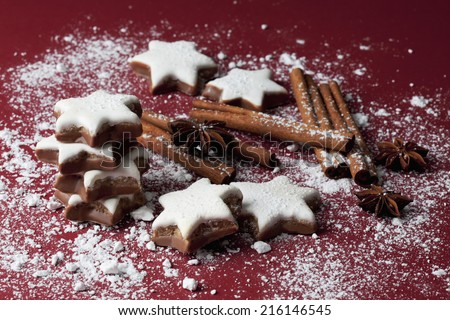 Cinnamon stars and spices sprinkled with powder sugar on red background - stock photo