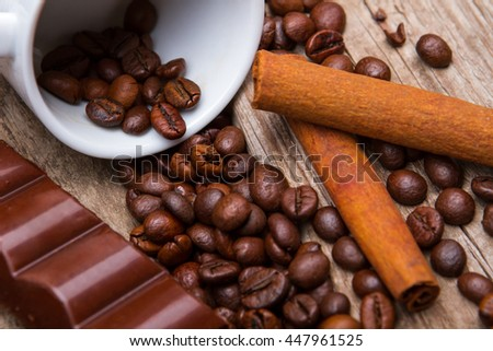 Cinnamon stick and coffee beans. Pieces of chocolate near cup. Milk chocolate of high quality. Ingredients for morning snack. - stock photo