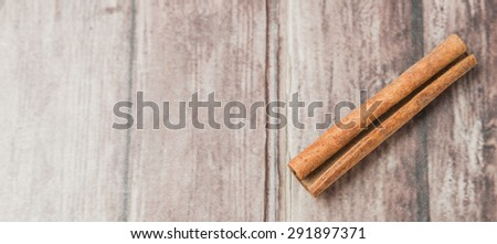 Cinnamon stick spice over weathered wooden background