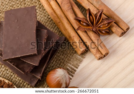 cinnamon stick, star anise and chocolate with nuts on wooden table - stock photo
