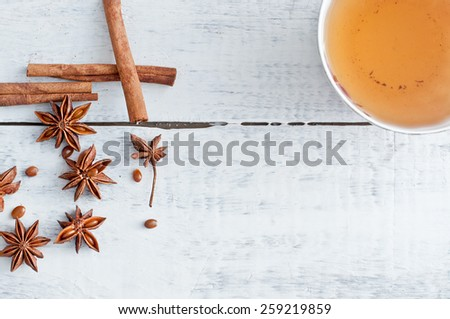 cinnamon stick, star anise and cup of tea on wooden table - stock photo