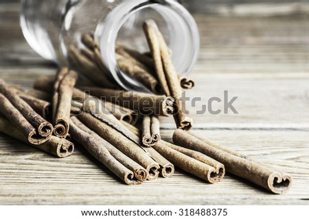 Cinnamon sticks and an jar on a wooden background