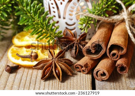 Cinnamon sticks and anise stars on christmas table. Beautiful candle holder in the background - stock photo
