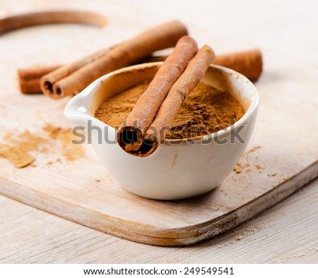 Cinnamon sticks and meal  on a wooden board. Selective focus - stock photo