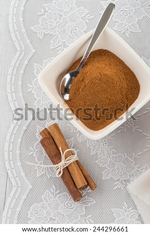 Cinnamon sticks and powder on ceramic bowl. - stock photo